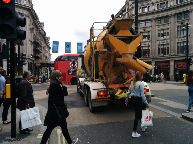 Big concrete mixer truck at a busy intersection